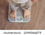 the boy stands on the scales to ... | Shutterstock . vector #1049066879