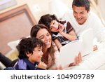 happy family reading a book in... | Shutterstock . vector #104909789