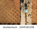 Small photo of Chrome padlock with dirty stain on skin locked rusty and scratch color metal door in sunset. Iron lock was worked with locking bracket and damaged old wire mesh door. Selective focus and vintage style