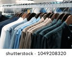 many shirts hanging on a rack ... | Shutterstock . vector #1049208320