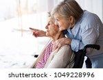 senior women with wheelchair at ... | Shutterstock . vector #1049228996