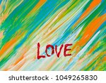 "Small photo of ""Love"" word. Drawn word ""Love"". Word drawn by acrylic white paint. Yellow, blue, green, orange abstract background. Brush stroke shape lines. Texture of paint. Motivation picture. Summer colors."