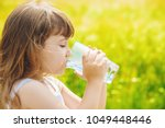 the child holds a glass of... | Shutterstock . vector #1049448446