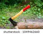 wood chopper sticks out in... | Shutterstock . vector #1049462660