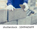 Bricklayer worker installing brick masonry on exterior wall with trowel putty knife - stock photo