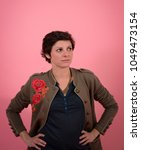Small photo of young woman up of face.American plan, which looks at the toptowards the left with hands on hips. Pink close background. Black short hair . natural skin
