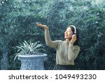 Girl teenager listening online music from headphone which connect smartphone application, standing in garden during snow falling down in winter. Smiling face and happiness emotion with relaxation.