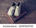 vintage white baby booties on a ...   Shutterstock . vector #1049550740