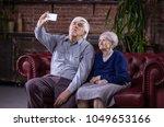 senior couple taking selfie... | Shutterstock . vector #1049653166