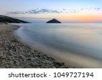 paradise beach at sunrise.... | Shutterstock . vector #1049727194