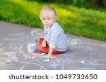 happy little kid boy drawing... | Shutterstock . vector #1049733650