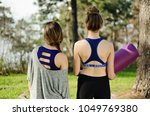 two young women in yoga clothes ...   Shutterstock . vector #1049769380