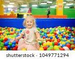 curly little girl having fun in ... | Shutterstock . vector #1049771294