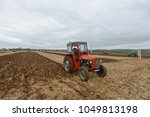 Small photo of Wingfield, UK - April 4, 2014: A vintage tractor pulls a plough through a farmland field. Widespread use of tractors emerged during mechanisation of the agricultural industry in the 1950s.