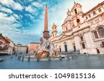 Fountain of the Four Rivers with an Egyptian obelisk and Sant Agnese Church on the famous Piazza Navona Square in the morning, Rome, Italy.