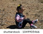 little girl sitting on the hill ... | Shutterstock . vector #1049905466