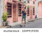 dad and son are tourists on the ... | Shutterstock . vector #1049919350