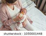 home portrait of a newborn baby ... | Shutterstock . vector #1050001448