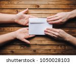 hands pass the white envelope... | Shutterstock . vector #1050028103