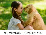 Stock photo child and golden retriever puppy girl is holding her young pet and they both looking into each 1050171530