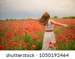 Small photo of Young woman in a white dress with red hair whorl in a poppy field. Happy girl is dizzy with joy. Copy space