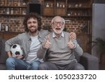 adult son hugging senior father ... | Shutterstock . vector #1050233720