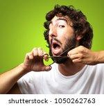 man cutting beard against a... | Shutterstock . vector #1050262763