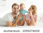 happy young family and infant... | Shutterstock . vector #1050276020