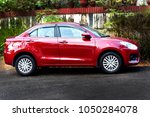 Small photo of TRIVANDRUM, KERALA, INDIA, MARCH 18, 2018: A Gallant red AMT Maruti Suzuki Dzire 1.2 VVT Allure Edition car parked by the roadside in front of a house.