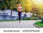 a beautiful sporty woman runing ... | Shutterstock . vector #1050295628