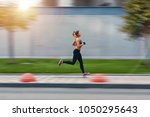 a beautiful sporty woman runing ... | Shutterstock . vector #1050295643