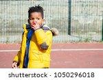 cute little boy with a yellow... | Shutterstock . vector #1050296018