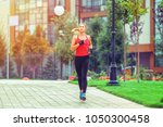 a beautiful sporty woman runing ... | Shutterstock . vector #1050300458