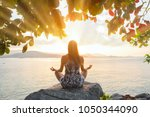 Small photo of Woman back side meditating sitting on big rock doing yoga in lotus pose under a tree and looking at the sun rays of the sunset, bright rays enlightenment, opening chakras bright colorful concept