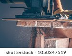 the worker cuts boards with an... | Shutterstock . vector #1050347519