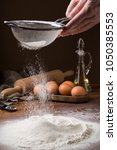 sifting flour from a strainer... | Shutterstock . vector #1050385553