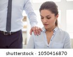 Small photo of Female abuse. Nice cheerless unhappy woman sitting in the office and looking at the male hand while being sexually harassed