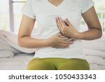 woman burning in the chest... | Shutterstock . vector #1050433343