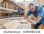 attractive man doing woodwork... | Shutterstock . vector #1050483146