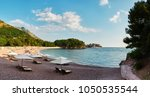 panoramic view on luxury sand beach with wooden chaise-longue chairs and umbrellas near the island Sveti Stefan town on the island. Montenegro