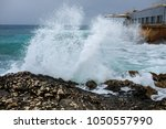 waves against rocks in the sea.    Shutterstock . vector #1050557990