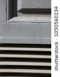 Small photo of Close up outdoor view of part of a grey painted door. Aeration system and mouldings are visible. Abstract architectural detail. Pattern of lines, shadows and geometric shapes. Graphic design.