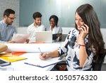 smiling business woman talking... | Shutterstock . vector #1050576320