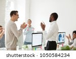Small photo of Happy motivated african american employee receiving envelope with reward or bonus from caucasian boss appreciating good work results while business team applauding supporting colleague in office
