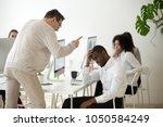 angry white boss scolding... | Shutterstock . vector #1050584249