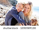 tourist mother and son on beach ... | Shutterstock . vector #1050589130
