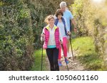 senior people nordic walking by ... | Shutterstock . vector #1050601160