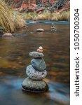 rock cairn in stream river... | Shutterstock . vector #1050700304