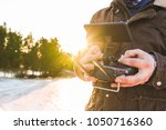 man holding in his hands remote ... | Shutterstock . vector #1050716360