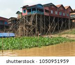 Small photo of High & dry at dry season these houses on sturdily constructed stilts sit above the river but when the rains come & the river rises the height above water level enables the residents to survive.